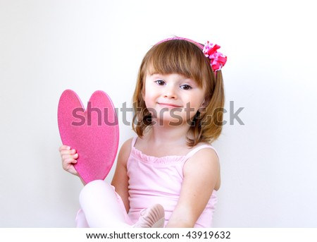 Little girl in pink holding a heart over the light background