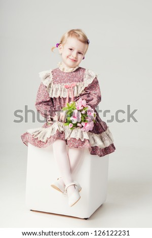 little girl in pink-violet dress and bouquet flowers. Small girl is sitting on a white pouf and holding bouquet of roses. Studio shot. Gray background