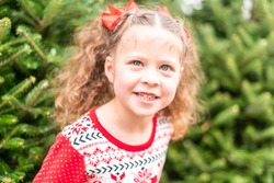 Little girl in red dress at the Christmas tree farm.