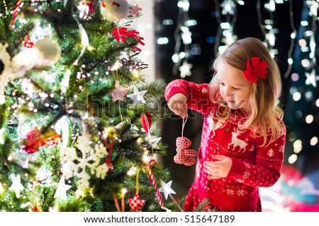 Little girl in red knitted Nordic reindeer sweater hanging ornaments on Christmas tree with light, bauble and candy canes. Child decorating Xmas tree in beautiful family living room with fireplace. #515647189