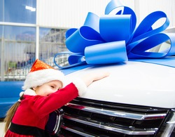 Little girl in red Santa Claus outfit hugs the car in front. Auto as a present with a big blue bow. The child's face is not visible