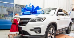 Little girl in red Santa Claus outfit hugs the car in front. Auto as a present with a big blue bow.