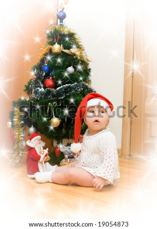 Little girl in red Santa hat wishing under christmas tree with snowflakes