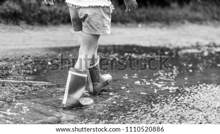 Stock Photo Little girl in rubber boots walking along the water after rain, ruined road, countryside, monochrome effect. Stories about rural life in Ukraine