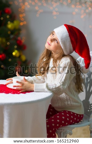 Little girl in santa hat drinking tea and dreaming at christmas night