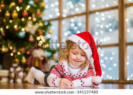 Little girl in Santa hat writes letter to Santa Claus #345137480