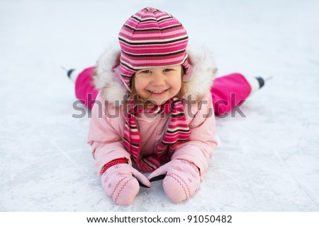 little girl in skates on the ice rink lies and laughs