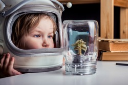 Little girl in space suit wearing helmet and discover plant in jar. Education for kindergarten and school children. Planet. Science. Dream to be astronaut. Curiosity child in botanical