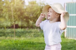 Little girl in straw hat on spring summer countryside, blonde kid spending time in nature at sunset. Nature background, rural landscape, green meadow, country style