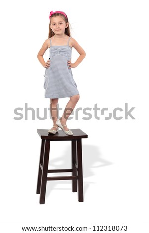 Little girl in striped dress stands on stool