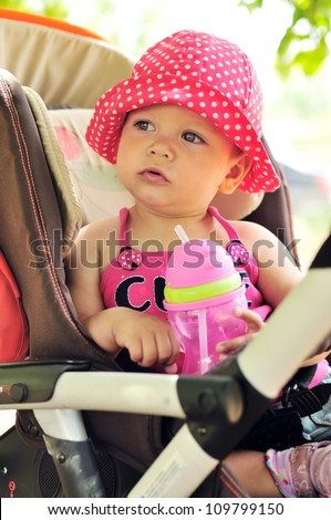 little girl  in stroller with bottle of water
