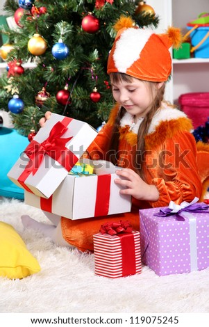 Little girl in suit of squirrels opens gift in festively decorated room