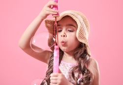 little girl in summer hat, blowing bubbles , on colored pink background, kids and summer concept