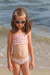 Little girl in sunglasses on sea background