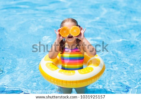 Little girl in swimming pool with inflatable toy ring eating orange. Kids swim on summer vacation. Tropical fruit and healthy snack. Swim aids for child.  Kid on colorful float. Beach and water fun.