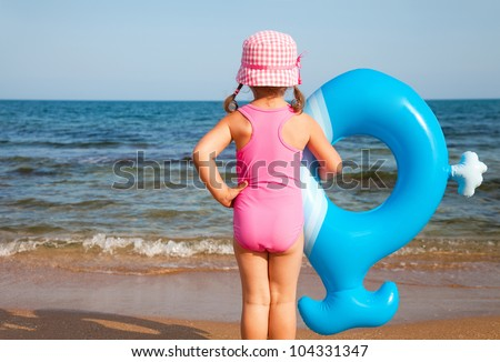 little girl in swimsuit looks at the sea and holds an inflatable toy