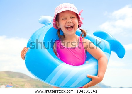 little girl in swimsuit playing with an inflatable whale on the beach