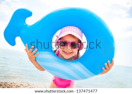 little girl in swimsuit playing with an inflatable whale on the beach resort