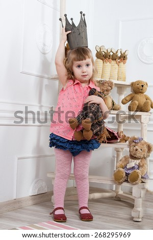 little girl in the crown among stuffed toys