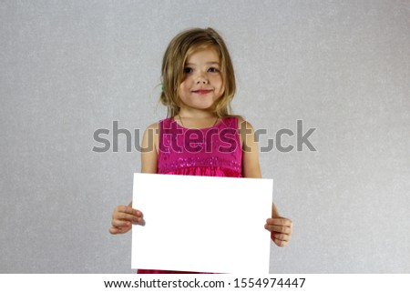 Little girl in the dress holds a white sheet of A4 paper horizontally, mock up.