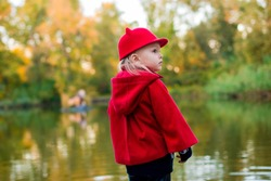 Little girl in the fall. Girl in a red coat near the pond.  Fashionable baby in a red coat for a walk. Beautiful girl outdoor. Stylish little girl in the fall. Baby in the autumn park