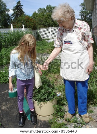Little girl in the garden with Granny - stock photo