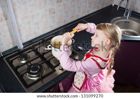 little girl in the kitchen putting pasta in the pot