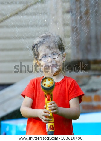 Little girl in the red shirt pours water from a hose