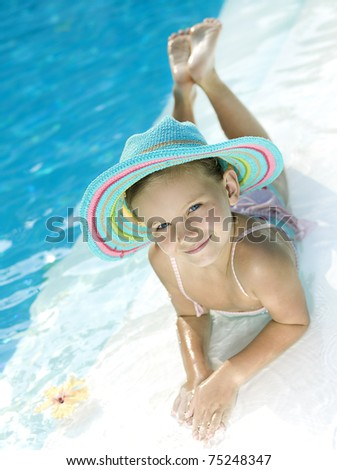 little girl in the swimming pool in hat looking at camera