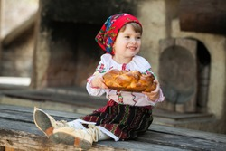 Little girl in traditional Romanian folk costume with embroidery. Girl in Romanian dress. Romanian folklore