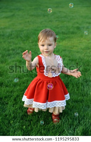 little girl in vintage red dress catches soap bubbles