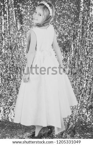 Little girl in white dress is posing in a beautiful studio. #1205331049