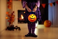Little girl in witch costume on Halloween trick or treat at home. Pumpkin and candle decoration of fireplace. Dressed up child trick or treating. Kid holding candy bucket. Kids celebrate Halloween.