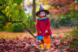 Little girl in witch costume playing in autumn park. Child having fun at Halloween trick or treat. Kids trick or treating.  Toddler kid with jack-o-lantern. Children with candy bucket in fall forest