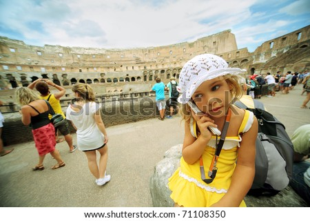 Little girl in yellow dress and white panama keeps electronic guide inside arena in Coliseum in Rome, Italy at sunny day