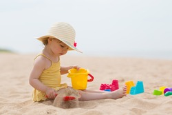 Little girl in yellow swimsuit and straw hat sitting on sand and playing with bucket and spade at sea beach in warm sunny summer day. Closeup. Side view.