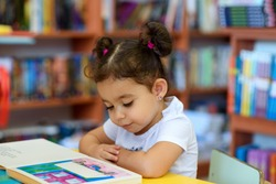 Little Girl Indoors In Front Of Books. Cute Young Toddler Sitting On A Chair Near Table and Reading Book. Child reads in a bookstore, surrounded by colorful books. Library, Shop, Shelving In Home.