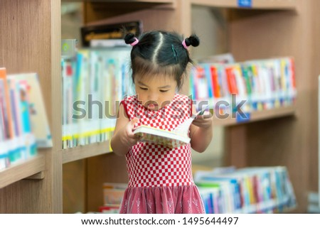 Little Girl Indoors In Front Of Books. Cute Young Toddler Standing Reading Book. Child reads in a bookstore, surrounded by colorful books. Library, Shop, Shelving In Home
