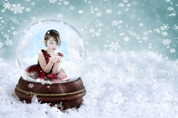 Little girl inside a Christmas snow globe blowing snow out of her hands. Copy space available. Shallow depth of field with selective focus on snowglobe.