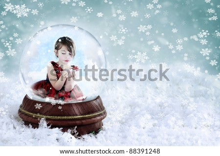 Little girl inside a snow globe blowing snow out of her hands. Copy space available.