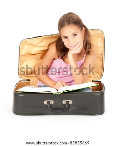 little girl inside a suitcase reading a book - stock photo
