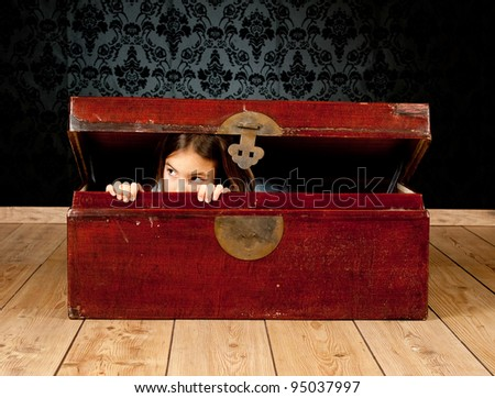 little girl inside an ancient trunk with a vintage background