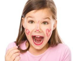 Little girl is applying lipstick on her cheek and nose, isolated over white