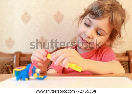 Little girl is at  table and models from plasticine, focus on  girl
