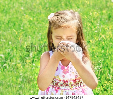Little girl is blowing her nose on green meadow allergy