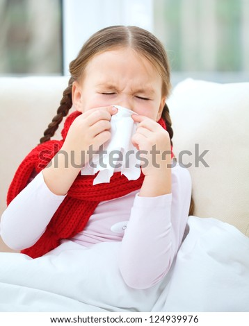 Little girl is blowing her nose while sitting on a sofa - stock photo