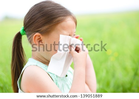 Little girl is blowing her nose while sitting on green meadow - stock photo