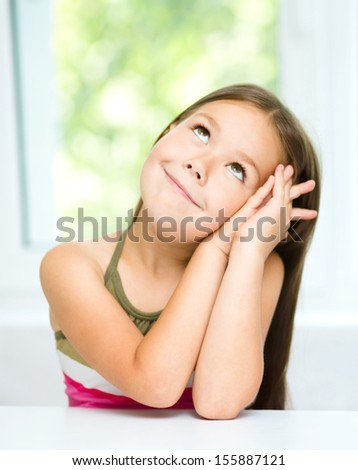 Little girl is daydreaming while sitting at table