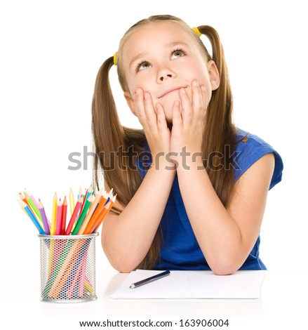 Little girl is daydreaming while sitting at table and drawing with color pencils, isolated over white