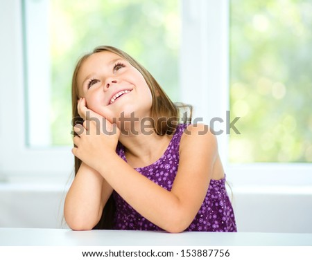 Little girl is daydreaming while sitting at table, isolated over white